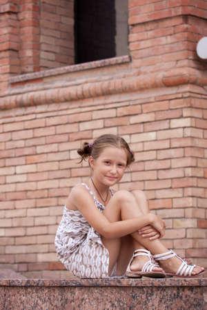 petite fille souriante couché sur un escalier de la construction urbaine.