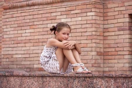少し微笑んでいる女の子が都会のビルの階段の上に横たわる。 写真素材