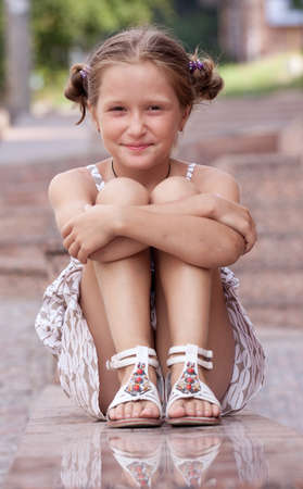 little town: little smiling girl lying on a stairs of urban building.