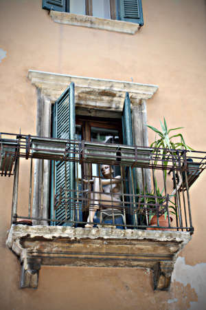 spanish houses: mannequin  sitting on balcony of italian town close-up .