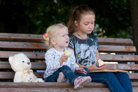 two sisters sitting  on a bench at the park. photo
