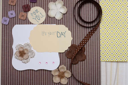 hand made scrapbooking post card and tools lying on a table. Banco de Imagens