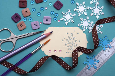 craft materials: hand made scrapbooking post card and tools lying on a table. Stock Photo