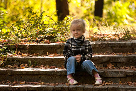 little smiling girl sitting on a stairs . photo