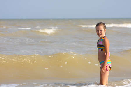 little smiling girl jumping in the sea. photo