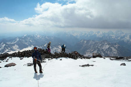 alpinist: climber walking up by the snowed glacier to the high summit