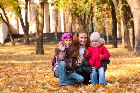 smiling mother with two daughters at the autumn park  photo