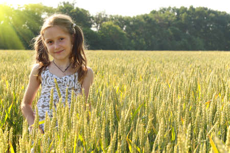 young girl joys on the wheat field