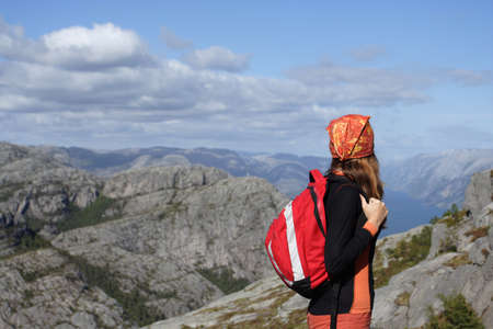 buff: girl hiker standing on a rock and looking at the mountains