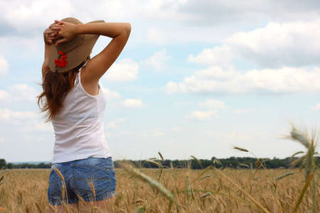 joys: young girl joys on the wheat field with blue cloudy sky at the background  Stock Photo