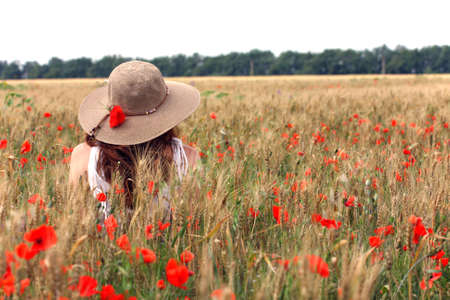 young girl sitting on the wheat field  Banque d'images