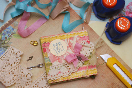 hand made scrapbooking post card and tools lying on a table