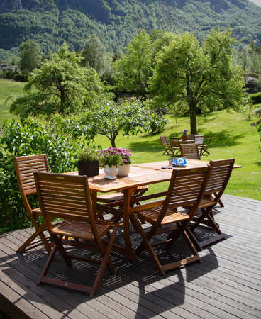 table and chairs standing on a lawn at the garden  Banco de Imagens