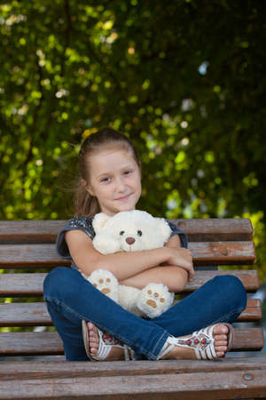 girl sitting  on a bench with teddy at the park  photo