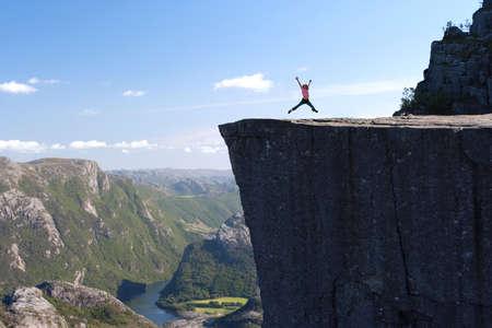 girl hiker jumping on Preikestolen, Preikestolen -famous cliff at the norwegian mountains  Stock Photo
