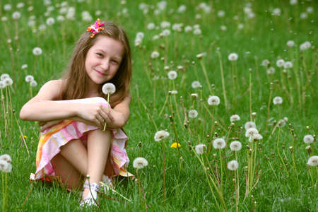girl with dandelion and green meadow in the background  Banco de Imagens