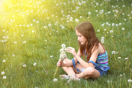 girl with dandelion and green meadow in the background  photo