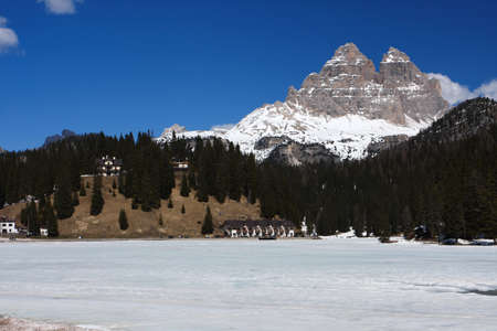 large frozen mountain lake with snowed mountains in the background, italy dolomites  photo