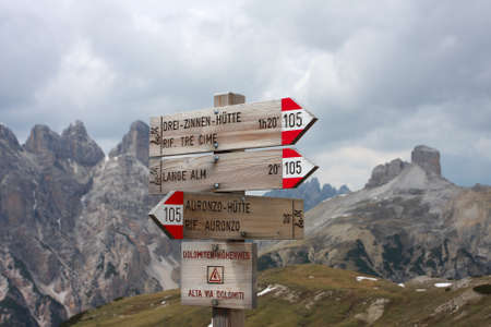 refuge: Alpine hiking trails hint along a trail, on background high rocky mountains, Italy
