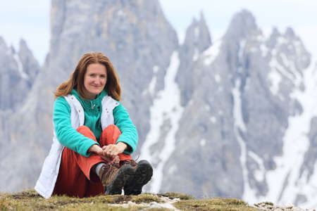 sitting smiling girl with the high rocky mountains at the background