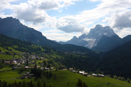 green valley with snowed mountains in the distance, Italy, Alps 