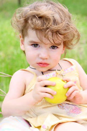 sitting child with the apple on a grass at the garden  photo