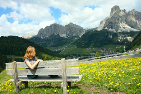 girl sitting on a wooden bench and looking at the mountains  photo