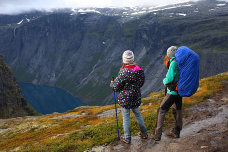 mother with her daughter hikers are standing on a path and looking at the fjord  Stock Photo