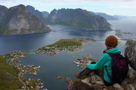 girl sitting on a cliff and looking at the Reine Stock Photo - 15812135