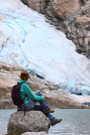 jostedalsbreen: girl hiker sitting on a stone and looking at the glacier