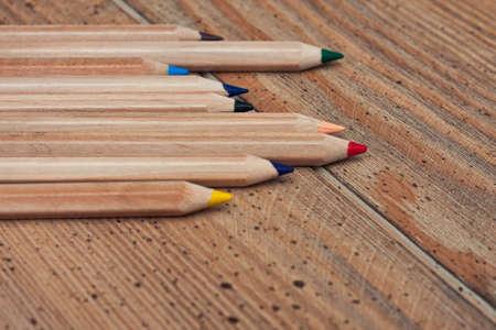 several multicolored pencils on a wooden desk  photo