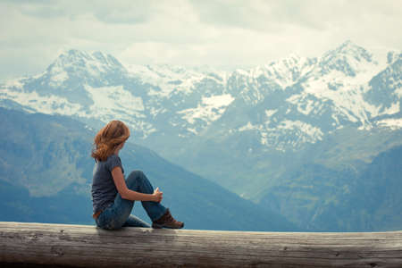 back country: girl hiker  sitting  and looking at the snowed mountains  Stock Photo