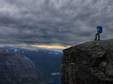 girl hiker standing on cliff and looking at the mountains, Preikestolen -famous cliff at the norwegian mountains  Stock Photo
