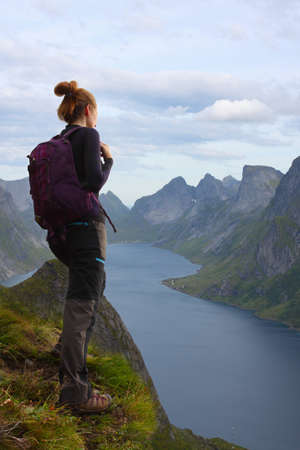 girl hiker standing on cliff and looking at the mountains,  lofoten, norway Stock Photo - 18151445