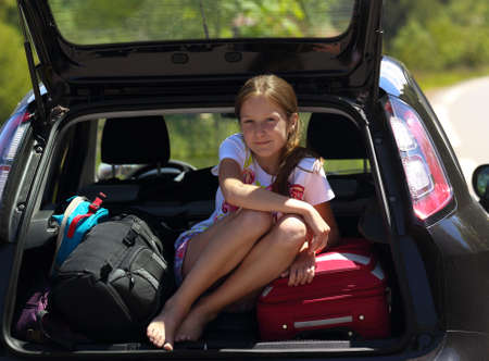 young  girl portrait at the car trunk  photo