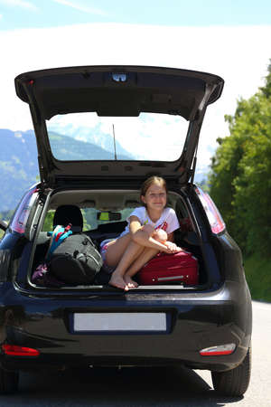 young  girl portrait at the car trunk