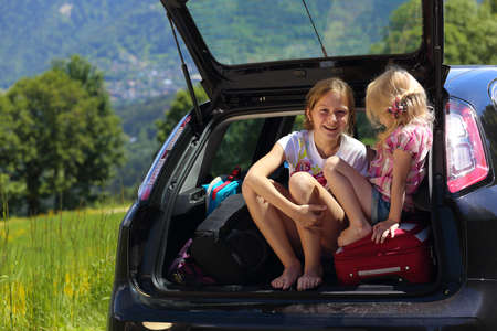 young  girls portrait at the car trunk  photo