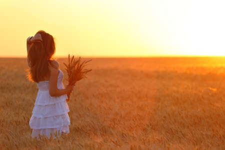 joys: young girl joys on the wheat field at the sunset time  Stock Photo