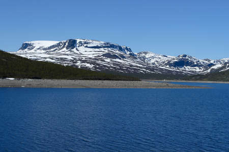 large mountain lake with snowed mountains in the background, norway  photo
