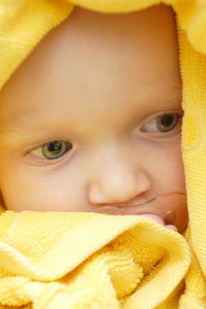 soother: portrait of baby girl covered by the towel after taking a bath