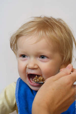 pap: little girl holding a spoon at her arms and eating a pap