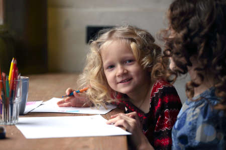 little girl drawing and looking at the camera  photo