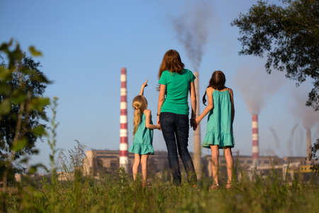 soil pollution: care future concept. Young mother with her kids are looking at the chimney-stalks polluting an air