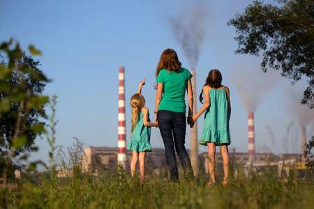 contaminacion aire: concepto futuro de atención. Joven madre con sus hijos están mirando a los chimenea-tallos un aire de contaminantes