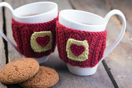 good weather: Knitted woolen cups on a wooden table