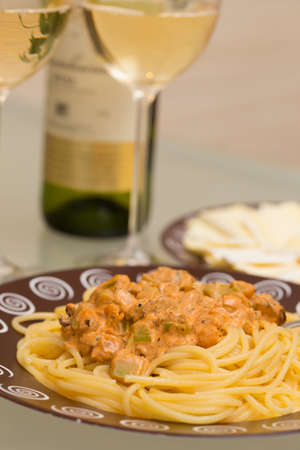 seafood pasta dish and white wine on a table