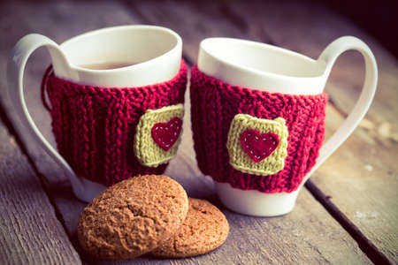 Knitted woolen cups on a wooden table  photo