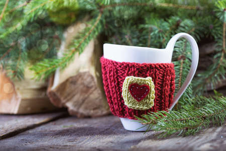 Christmas Decor. Knitted woolen cups with bokeh at the wooden table photo