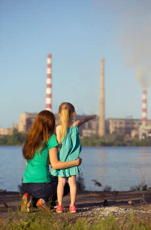 polluting: care future concept. sisters are looking at the chimney-stalks polluting an air