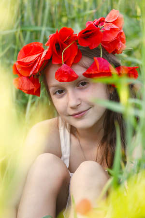 circlet: close up portrait of child girl with circlet of poppies sitting at the grass Stock Photo
